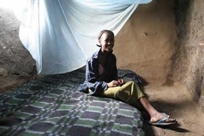 child beneath bed net