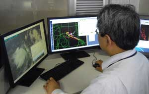 man in front of computer screens