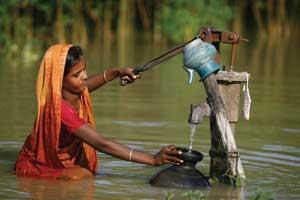 Woman getting water in flood - © OECD