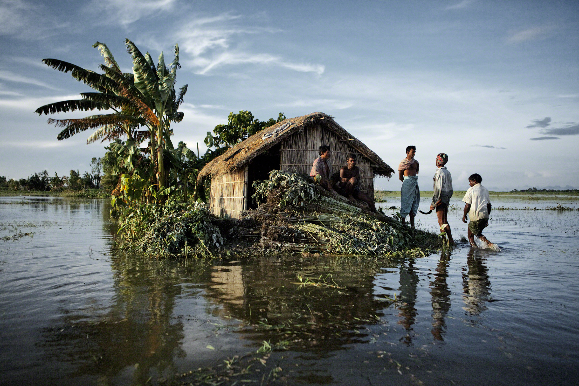 Gaibandha District, Bangladesh, 2010. During the harvest of jute, villagers rest above the floodwaters of the surging Brahmaputra River. A simple adaptation in flood-prone areas is building every house on a two-meter tall mud plinth. Photo: Jonas Bendikse