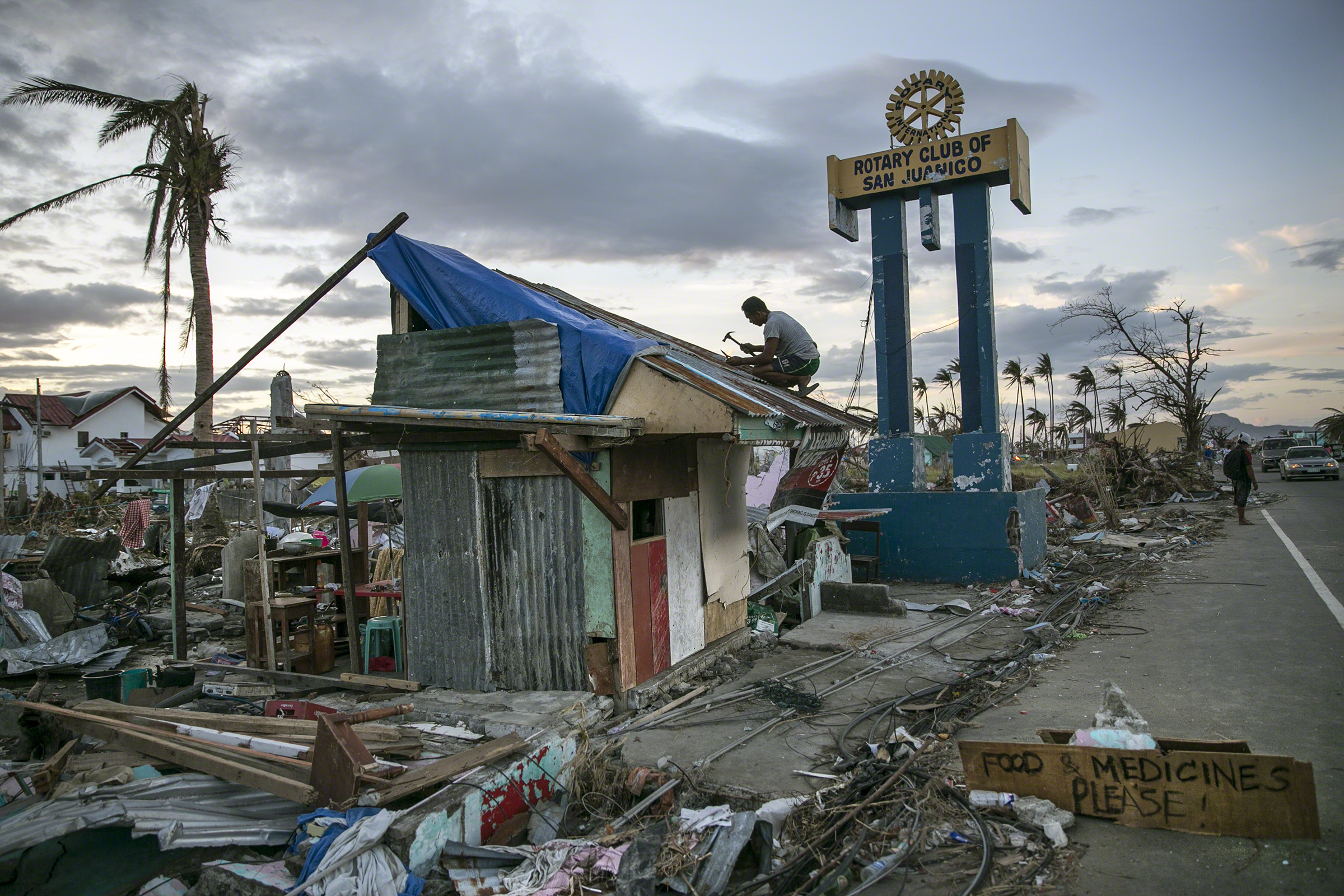 Tacloban, Philippines, 20 November 2013. A man hammers away amidst the destruction caused byTyphoon Haiyan (also known as Yolanda), which hit the islands of Leyte and Samar on 8 November 2013. Photo: Paula Bronstein/Reportage by Getty Images