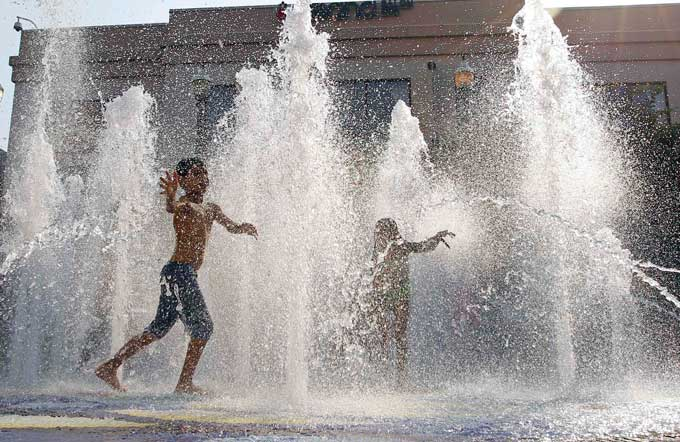 children playing in fountain on a hot day