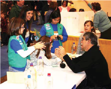 A DataStreme course leader conducts a weather experiment with a group of youth at WeatherFest.