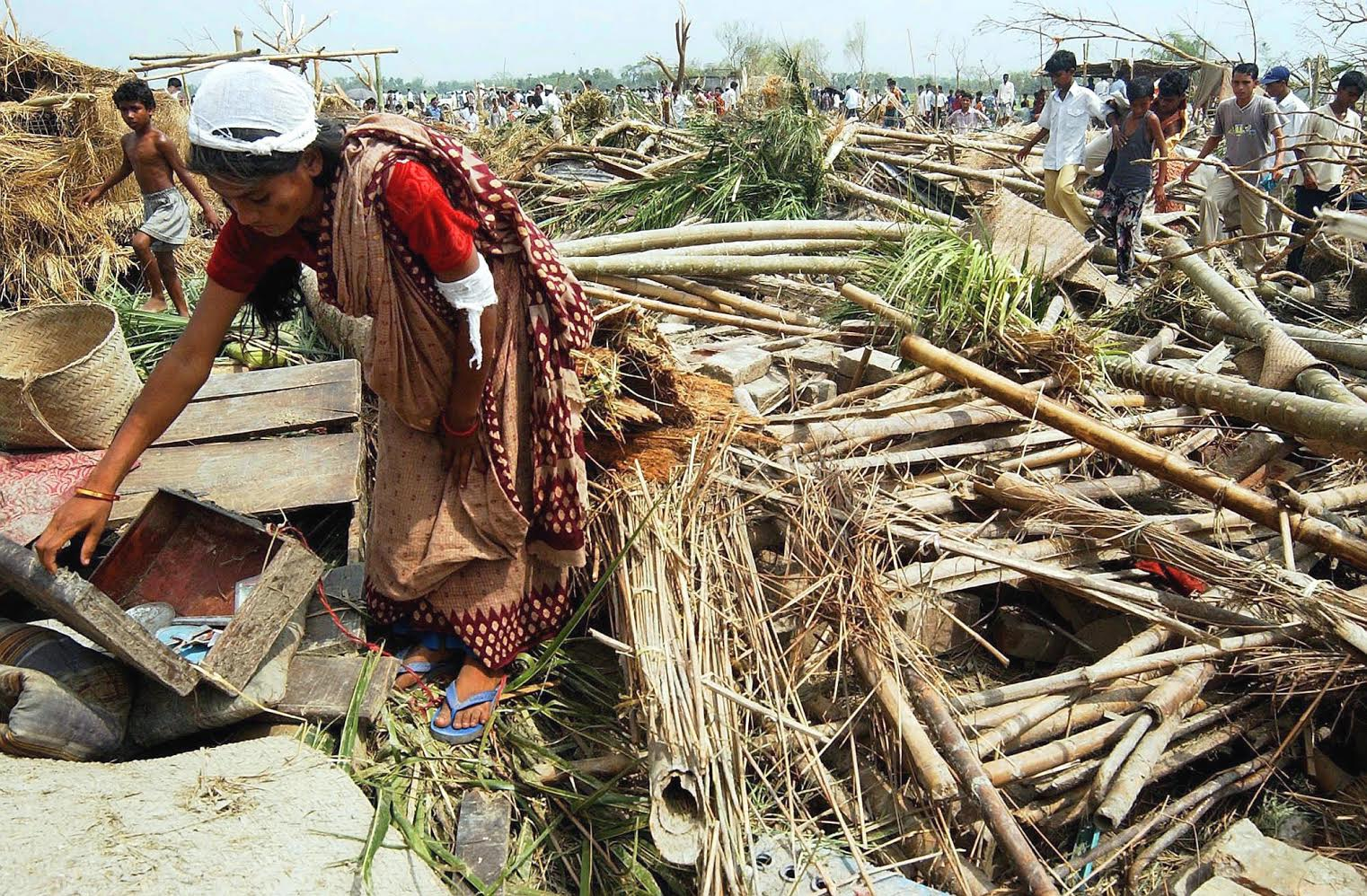 A Bangladesi women looking for her belongings in the debris of her house in the village of Kachanpur, Netrokona district in nort