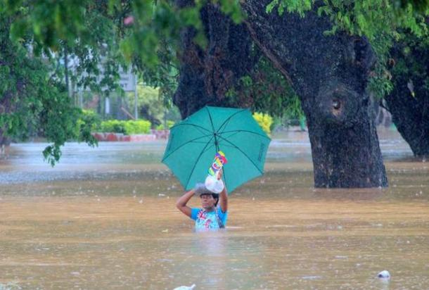 Residents of Korociri settlement cross through the flooded Nadi backroad in Fiji. Photo: Fiji Government