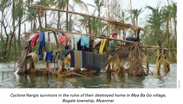 Cyclone Nargis survivors in the ruins of their destroyed home in Mya Ba Go village, Bogale township, Myanmar