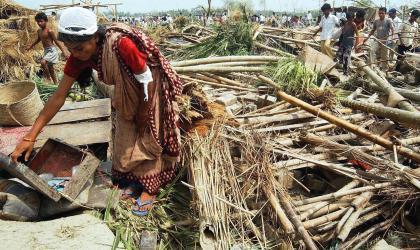 A woman in the debris of her house in Kachanpur in NE Bangladesh. Photo epa/Mufty Munir