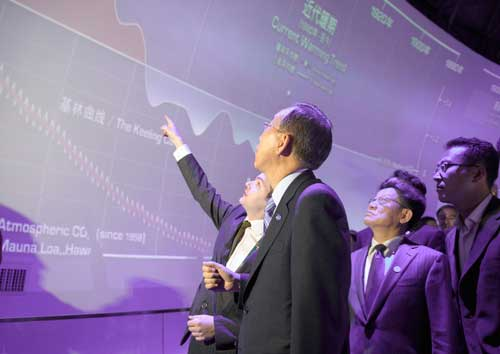 Secretary-General Ban Ki-moon (front) is shown a graph with climate change and current weather trends